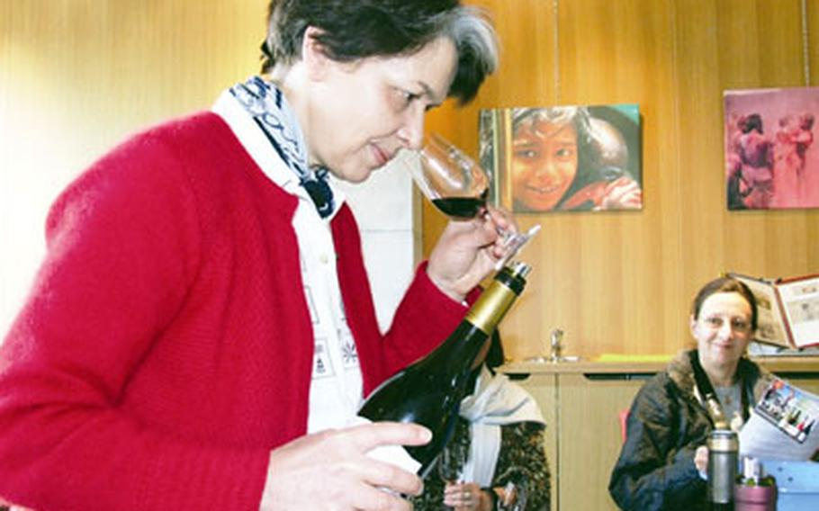 Caroline Rinaldi at Cave de Rasteau sniffs the bouquet of a Cotes de Rhone red wine during a group tasting. She said the cooperative hopes to have its red wines elevated to cru status soon.