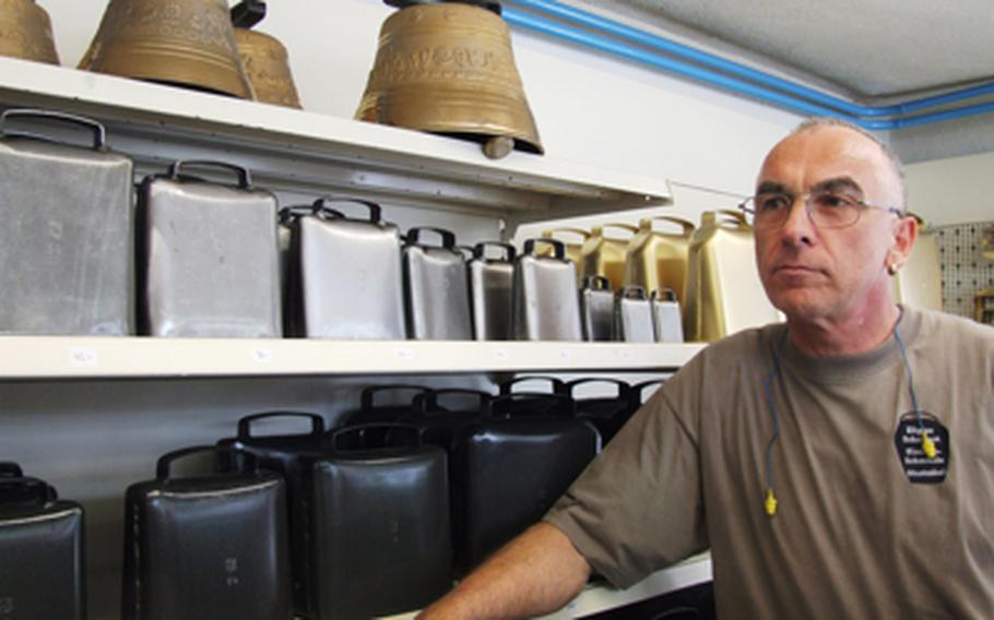 Eligius Schelbert poses with some of his bells he has made in his shop in Muotathal, Switzerland. He makes three types of bells in 15 sized, yet he claims that when he is in the mountains that he can recognize the sound of his bells.
