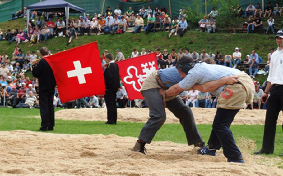 """""""Schwingen"""" wrestlers hang onto their opponent's shorts as they try to throw the other to the ground and then his shoulder while still hanging onto his shorts. Flag throwers, who entertain the spectators between bouts, await their turn to perform."""