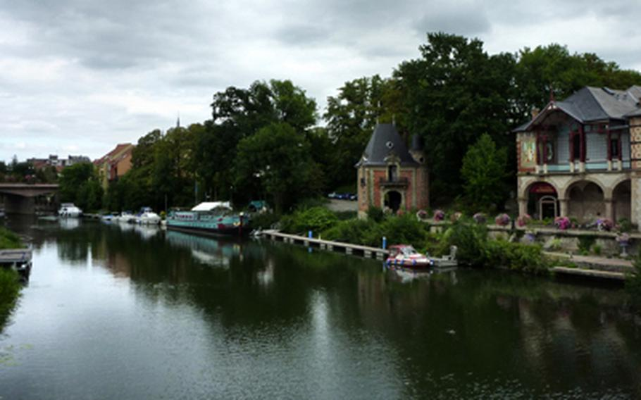 The waterfront of the French town of Sarreguemines is lined with picturesque buildings and a variety of water craft.