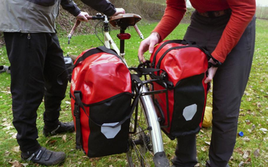 Luke Stover attaches a waterproof pannier to his bike rack after a night of camping at a site near Schönenberg-Kübelberg in Germany.  A rear bike rack and panniers are the nuts and bolts of carrying gear on a bike tour.