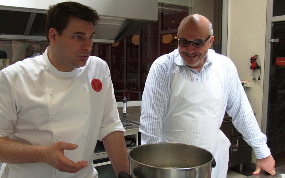 Jack Bussy, left, who attends the L'atelier des Chefs lunchtime cooking classes two to three times a week, listens as chef-instructor François Pelletier gives tips on preparing pasta for Farfalle au Canard, Citron et Câpres.