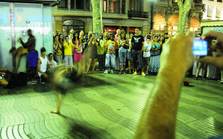 Street performers busk on Las Ramblas, one of the main attractions of walking down Barcelona's main street.