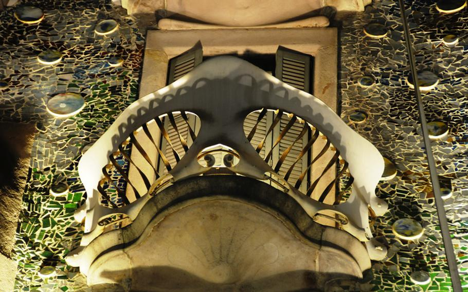 A close up of one of the balconies on the front of Batllo House in Barcelona; designed to look like a mask or skull with cut-out eyes and a mouth.