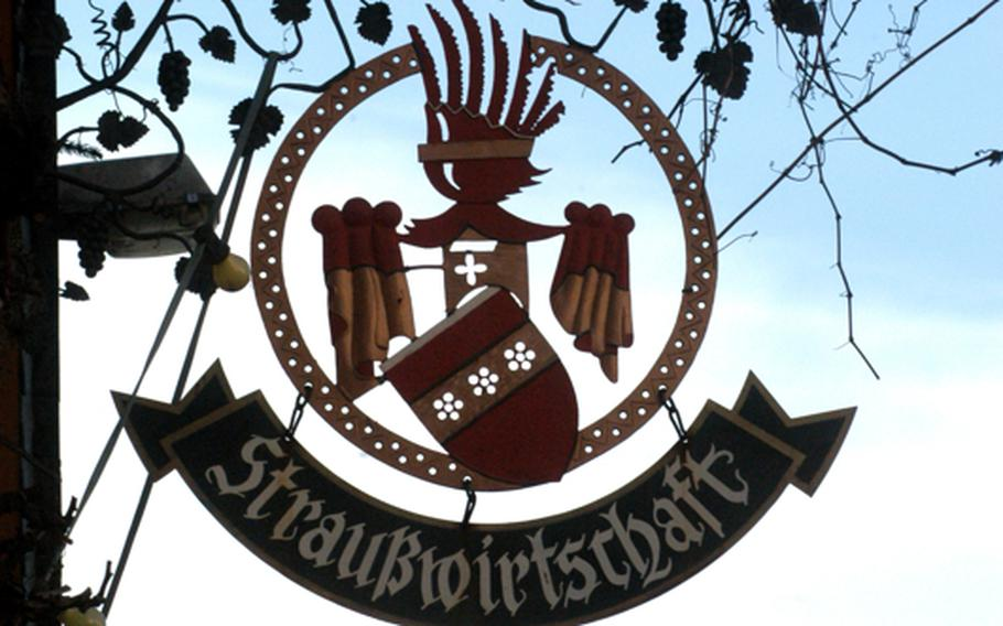 An elaborate sign advertises a local wine tavern where a vintner can sell his own wines. Along the Weinstrasse, these inns are known as Strausswirtschaften.