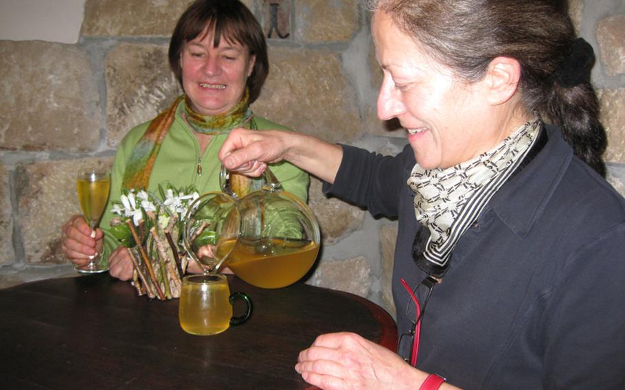 Joyce Lambert of Echterdingen, Germany, gets a fresh glass of Riesling from Gerlinde Zaiss at the Sonnenbesen. The winemakers often serve the wine via pitchers filled from a large cask.