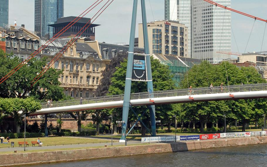A pedestrian bridge crosses the Main River with Frankfurt's financial district  in the background.