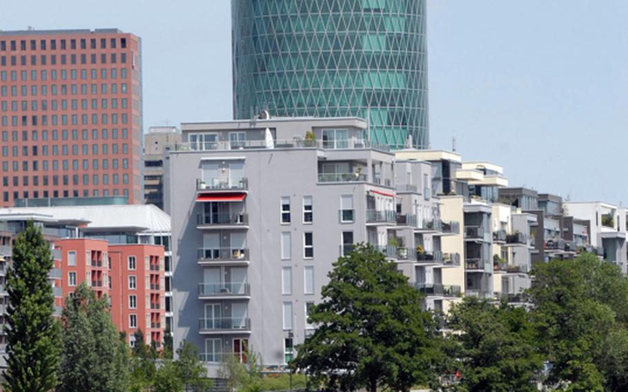 """A building dubbed by residents as """"the world's tallest apple-wine glass"""" towers above the banks of the Main River in Frankfurt.  Apple wine is a drink with roots in the region and is a popular summertime choice for city residents."""