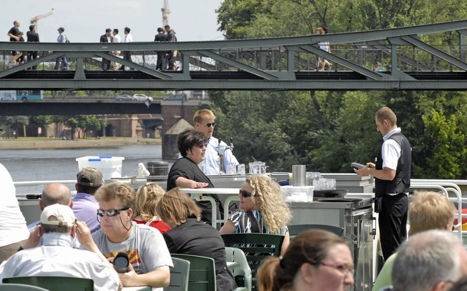 Guests sip drinks and take in the sights of Frankfurt from the sun deck on a Main River cruise.