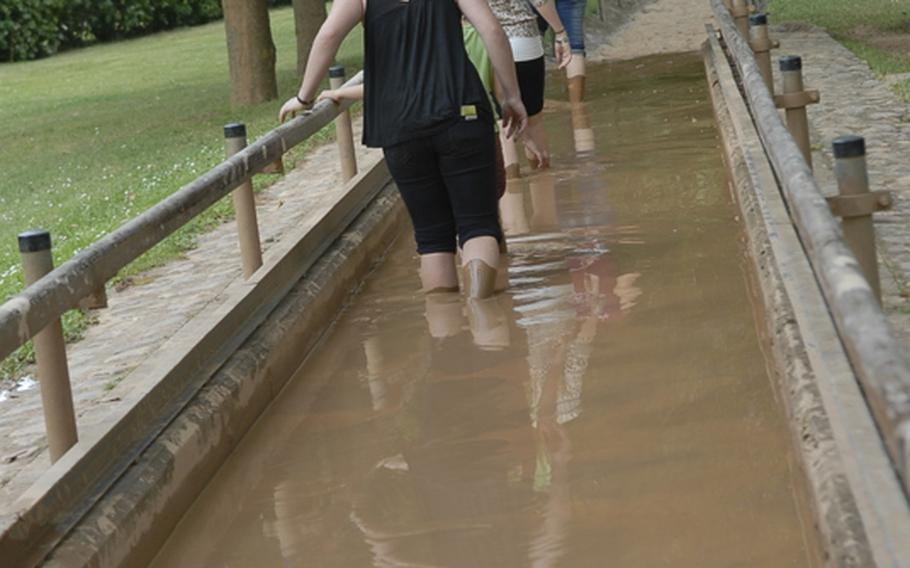 Walkers trudge through the mud basin at the barefoot park. The clay-rich mud is supposed to be good for the skin.