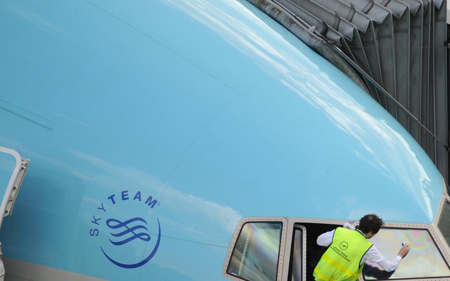 A member of the ground crew at Frankfurt Airport cleans the cockpit windshield of a Korean Air jet.