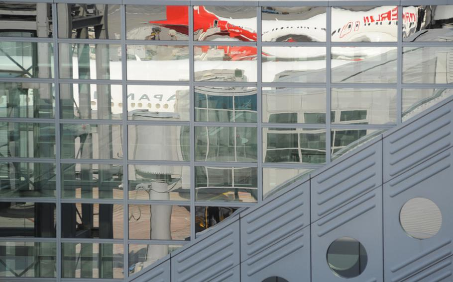 Jets from Air Berlin and Japan Airlines are reflected in the window of Frankfurt Airport's Terminal 2.