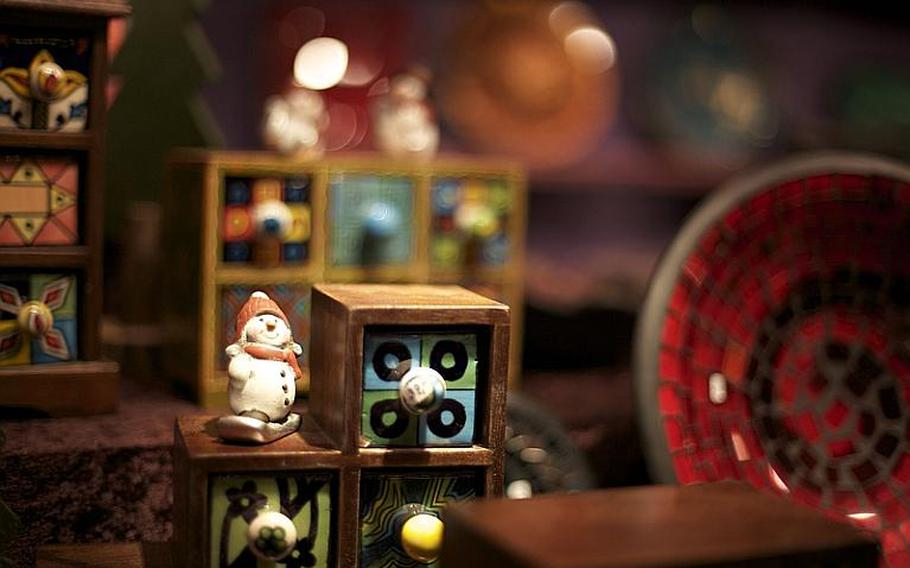 Hand-painted toys, colored glass and decorative ceramics brighten a display at Bonn's Christmas market.
