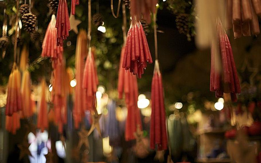Handmade candles hang in a shop stall.