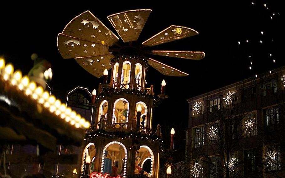 A Christmas pyramid featuring wooden toys the size of small men towers in a corner of Bonn's Christmas market.