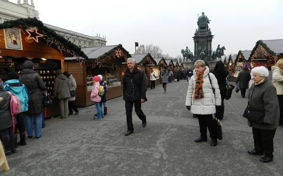 A stately monument to the 18th century Austrian ruler Empress Maria Theresa, seen in the background, reigns over the Christmas Village market at Maria-Theresian-Platz in Vienna. The market is nestled between two of the city's most famous museums, the Art History Museum, seen partially on the left, and the Museum of Natural History.