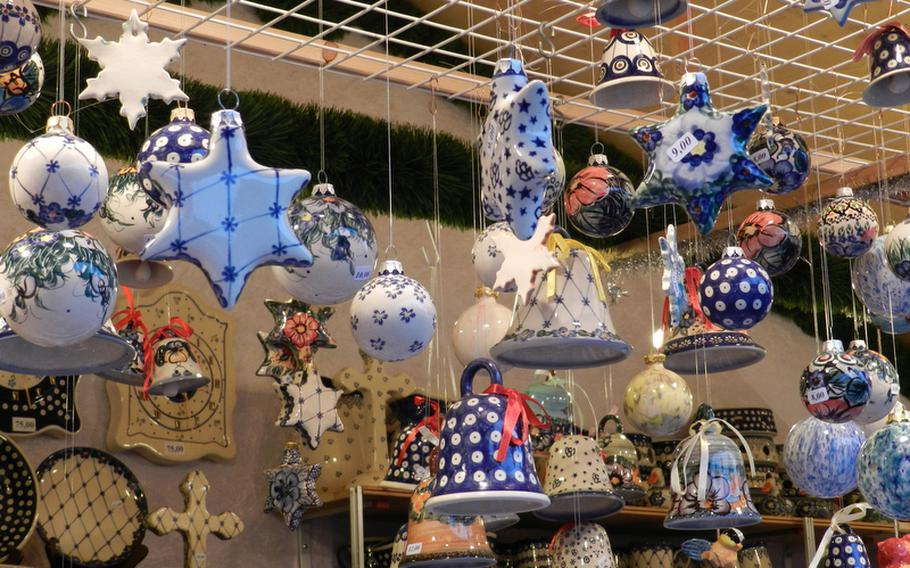 Polish pottery decorations in traditional as well as new patterns hang from a vendor's stand at a market in Vienna, Austria.