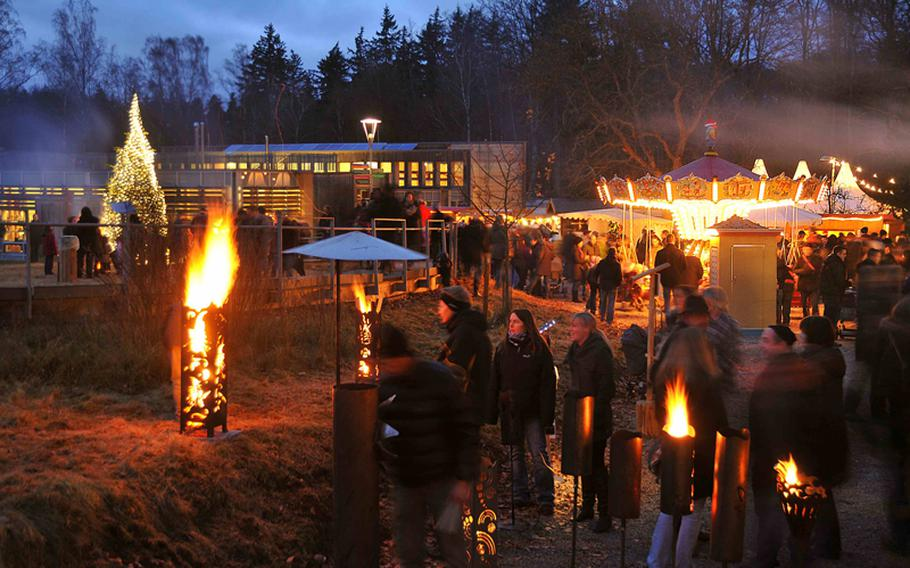 Bonfires and torches provide most of the lighting at the Johanniskreuz Romantische Waldweihnacht near Kaiserslautern, Germany. The Christmas market, sponsored by the House of Sustainability, seen in the background, is an environmentally friendly holiday market in the forest. Dates this year are Dec. 15-16.