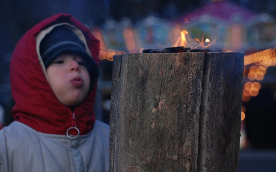 """A child blows on a """"Schwedenfackel"""" (Swedish torch), one of many used to warm the crowds at the market."""