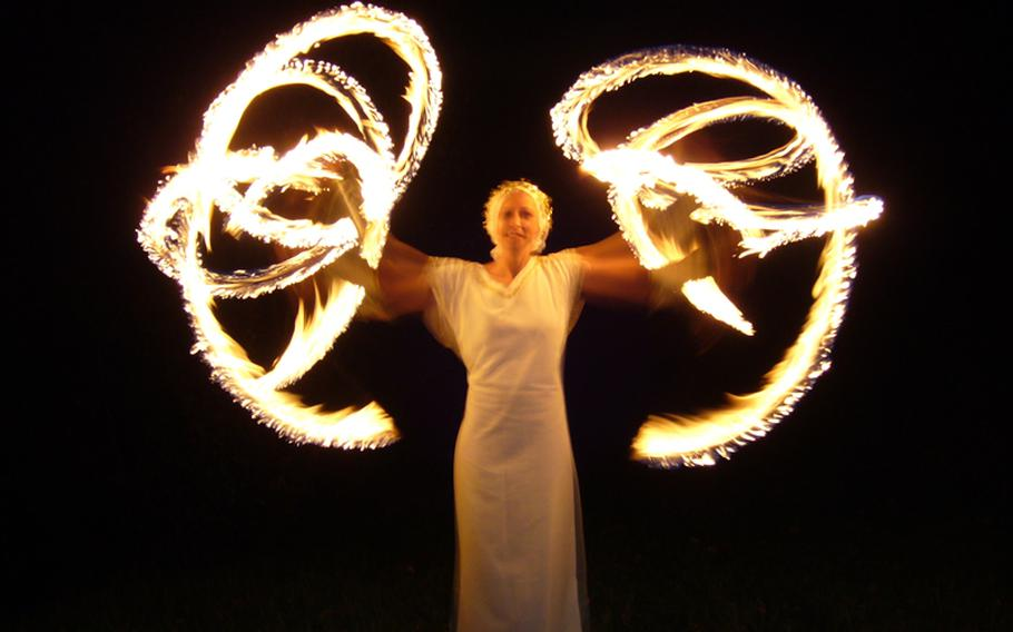 """A """"fire angel"""" performs with torches at the Johanniskreuz Romantische Waldweihnacht. The fire show this year takes place at 7 p.m. Dec. 15."""