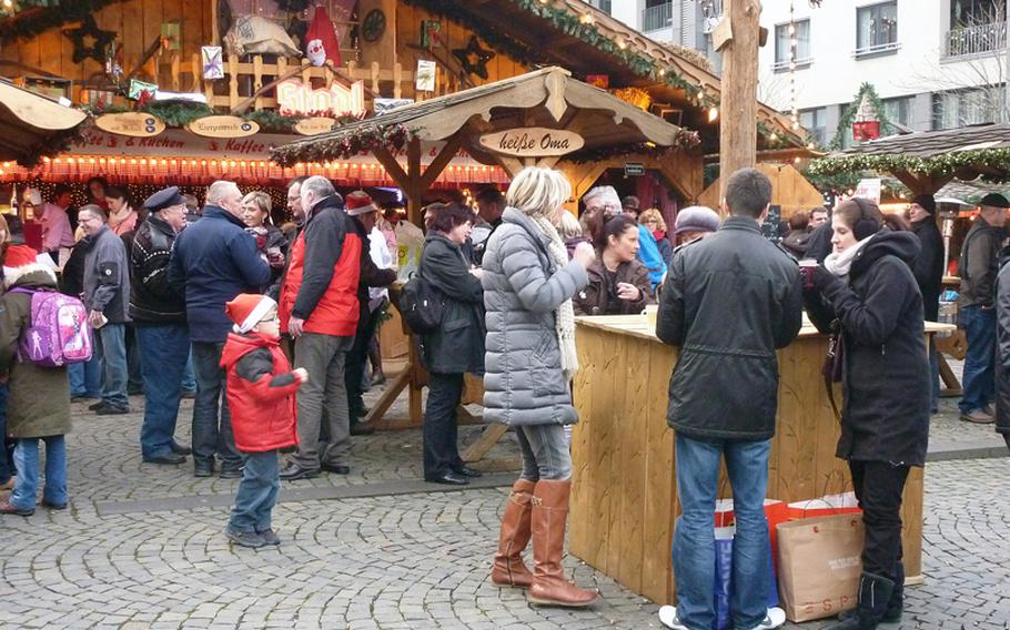 Visitors enjoy food and drinks on the Münzplatz in Koblenz, Germany, during the city's Christmas market.