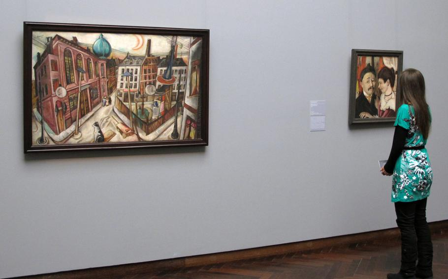 """A visitor to the Städel modern art collection in Frankfurt, Germany, looks at Max Beckmann's """"Portrait of the Carls."""" At left is his """"Synagogue in Frankfurt am Main,"""" one of his most famous paintings."""
