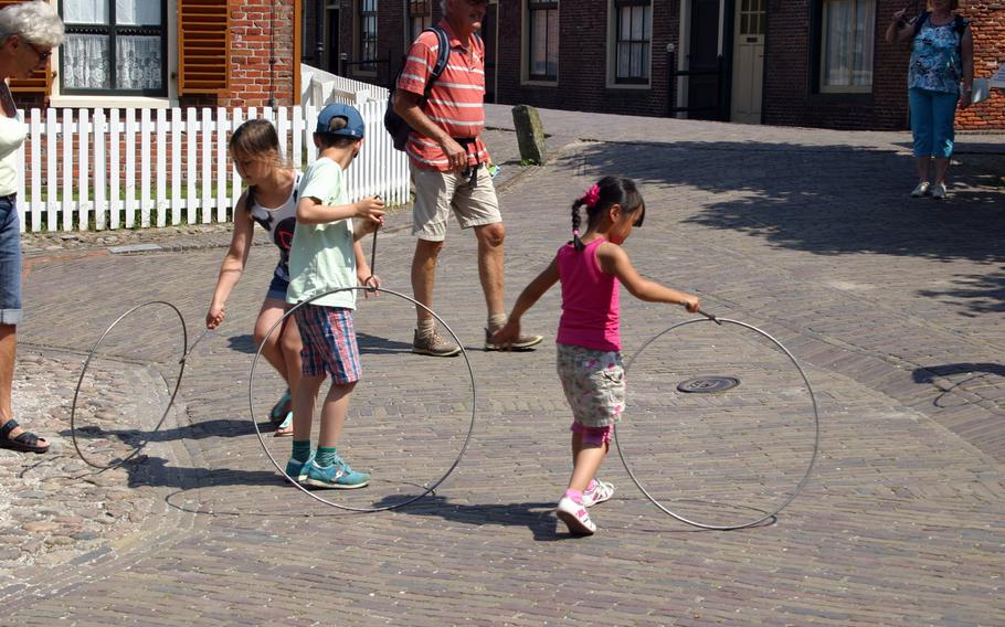 Children learn how to roll hoops, just like kids did a century ago, during a visit to the Zuiderzee Museum in Enkhuizen, Netherlands.