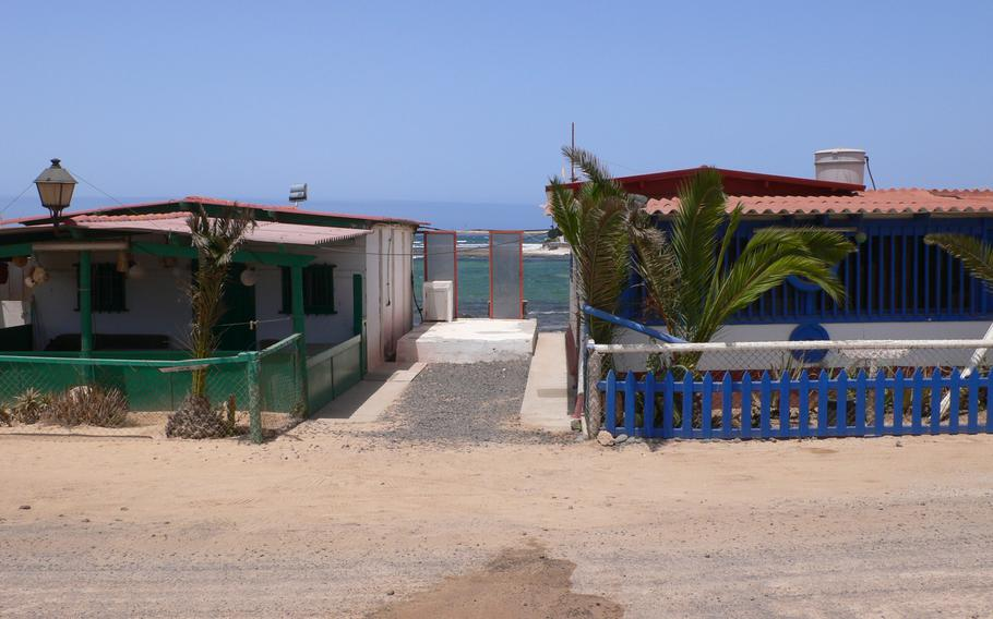 Beach houses such as these in the remote fishing village of Majanicho, on the island of Fuerteventura in the Canary Islands, have a perfect view of sand and sea.