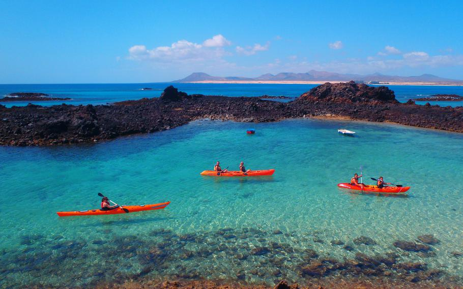 Sunshine and crystal-blue waters invite kayakers to the island of Fuerteventura, in the Canary Islands.