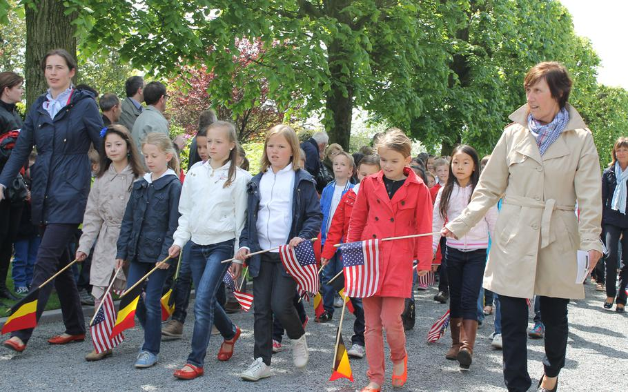 """Waregem, Belgium, schoolchildren join the parade entering the Flanders Field American Cemetery. They sang """"The Star-Spangled Banner"""" during the Memorial Day service."""