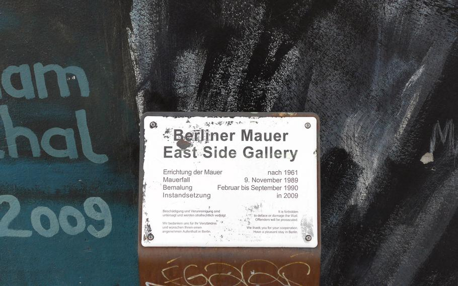 A plaque on the Berlin Wall marks its history and that of the East Side Gallery, the art exhibit that now decorates the Cold War relic. Built after 1961; fell Nov. 9, 1989; painted February to September 1990; renovated in 2009.