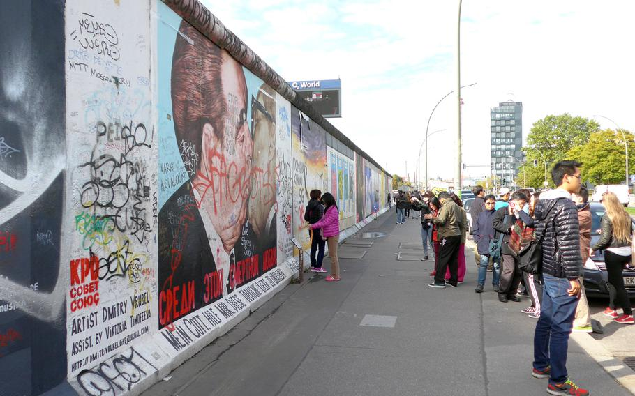 Tourists at the East Side Gallery are photographed in front of artist Dimitri Vrubel's mural of former Soviet leader Leonid Brezhnev and East Germany's Communist Party leader Erich Honecker kissing. The work is based on a photo by French photographer Regis Bossu, who also spent time as a Stars and Stripes photographer.
