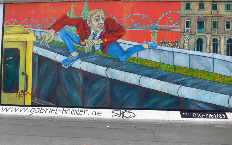 """Gabriel Heimer's """"Mauerspringer,"""" or """"Wall Jumper,""""  on the East Side Gallery depicts a man jumping over the Berlin Wall. The gallery is one of the largest open-air galleries in the world, with more than 100 original murals."""