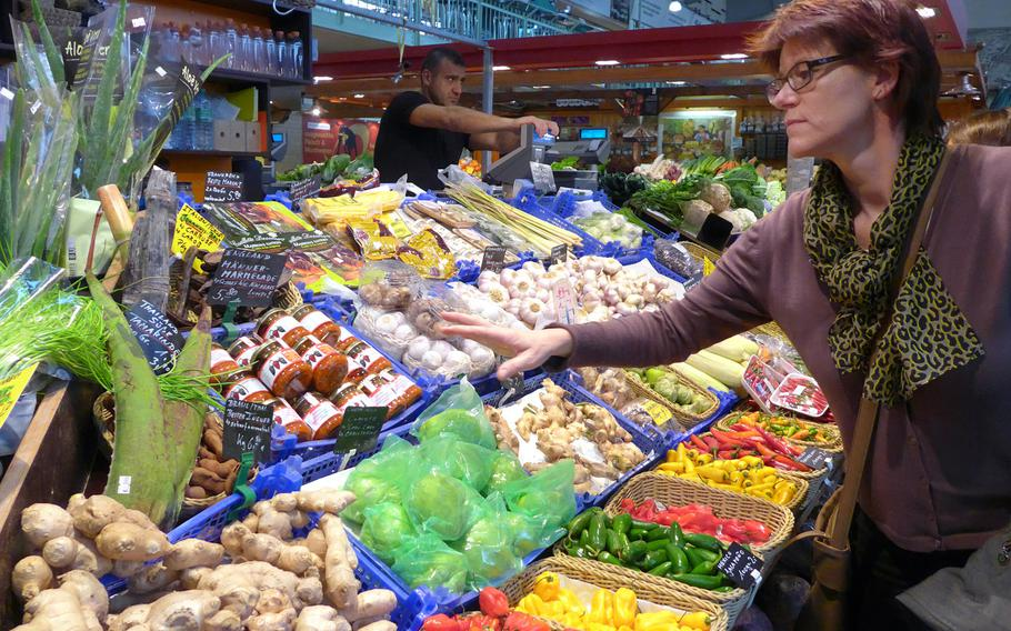 A customer inspects the goods at the Kleinmarkthalle in Frankfurt, Germany.