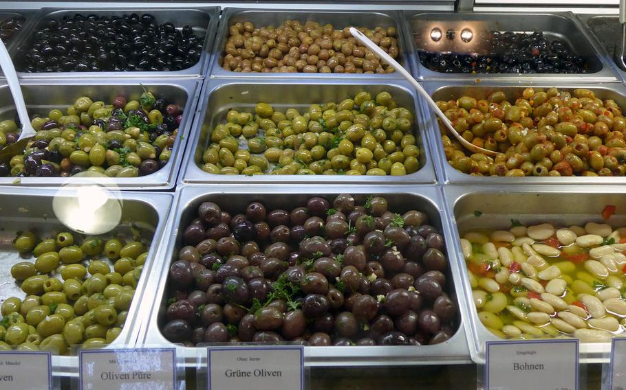 A stand specializing in Middle Eastern food offers various types of olives.