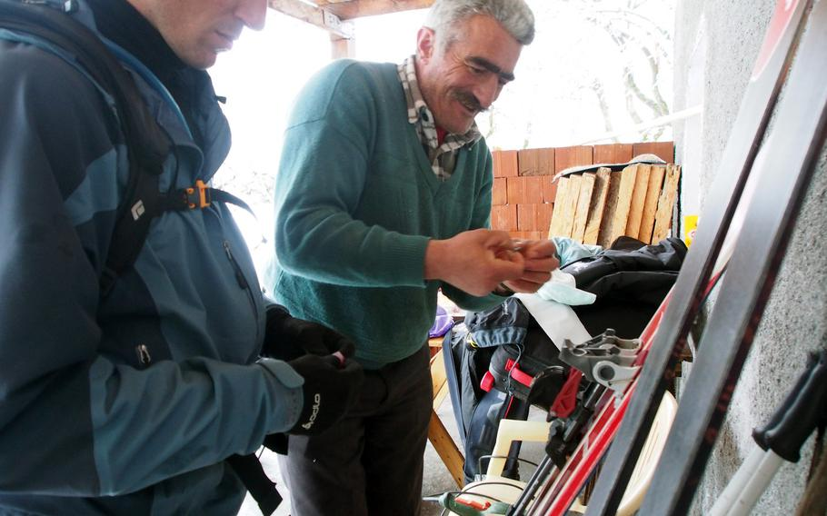Kol Gjoni, right, helps with an emergency ski repair in Valbona, Albania.