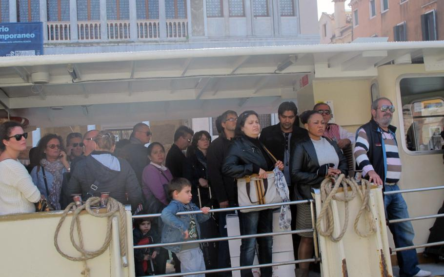 """Water taxis or """"vaporettos,"""" at 7 euros a ticket, are the most economical, if  unglamorous, way to go in Venice. Here, people are waiting at a stop."""