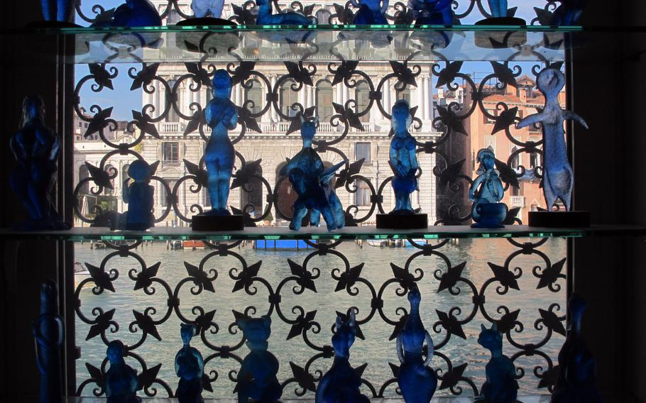 Blue glass sculptures created by Egidio Costantini, inspired by Picasso, are displayed in a window of the Peggy Guggenheim Collection overlooking the Grand Canal in Venice.