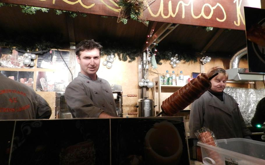 A vendor at the Winter Wonderland in Hyde Park shows off his Christmas cake made on a rod.