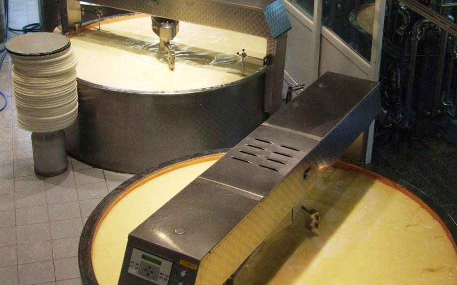 Gruyère cheese in the making in Gruyère, Switzerland. Rotating blades cut the curdled mass, which is then heated. Once the particles have dried, the mass is poured into molds.