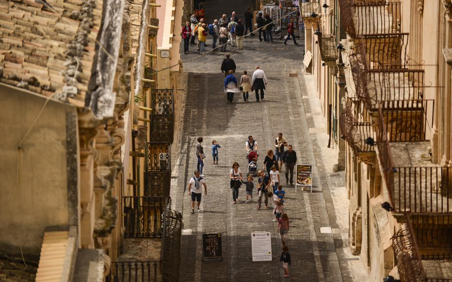 Tourists wander the peach-colored Baroque city of Noto, Sicily.