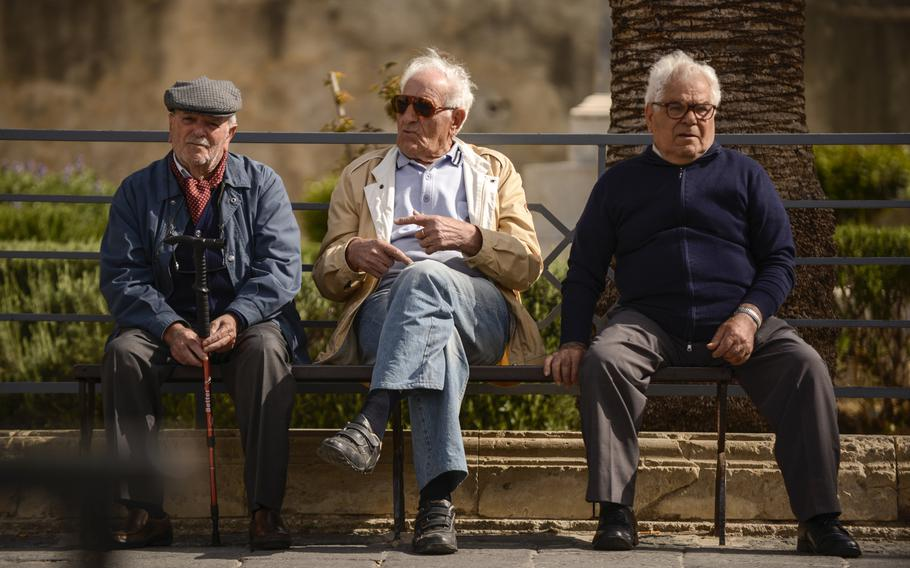 Local residents with no particular place to go have a morning chat in Noto, Sicily.