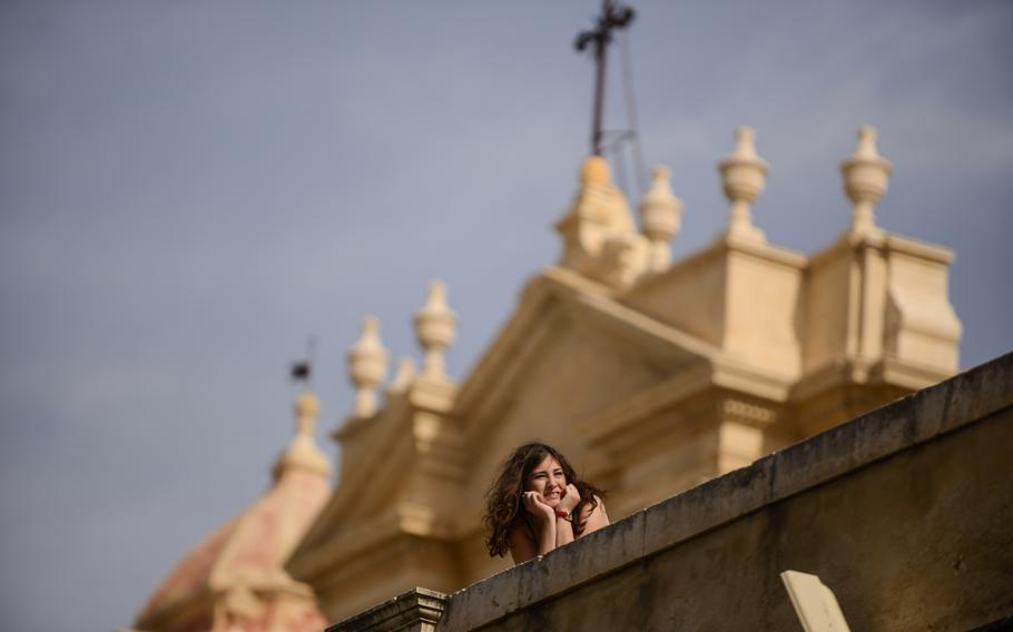 A woman looks down Noto's main street with the Noto Cathedral in the background in Noto, Sicily.