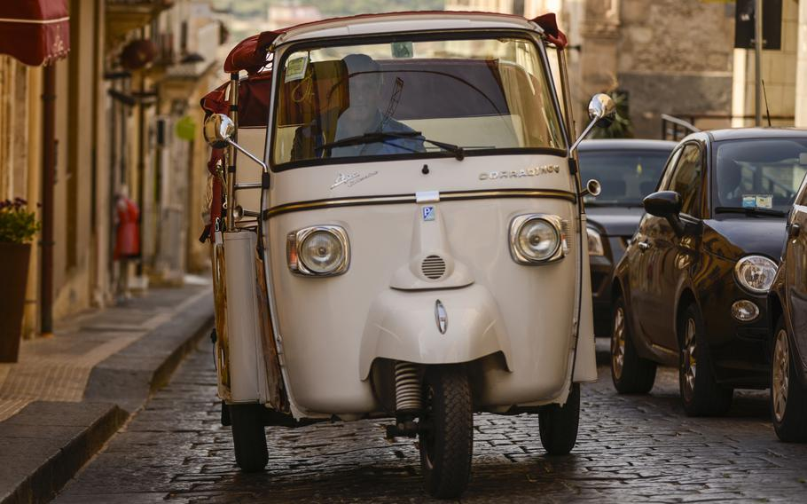 A tour guide in Noto, Sicily, drives his Piaggio Ape, a three-wheeled, light commercial vehicle first produced in 1948.