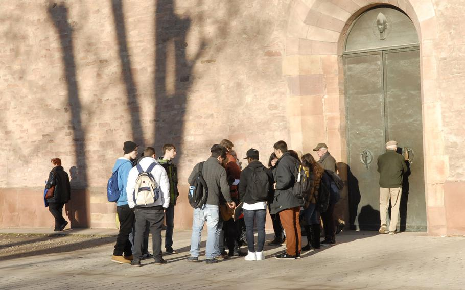 Visitors to the Speyer cathedral  gather outside a nondescript entrance to the old basilica: an unmarked side door. Entrance to the cathedral is free.