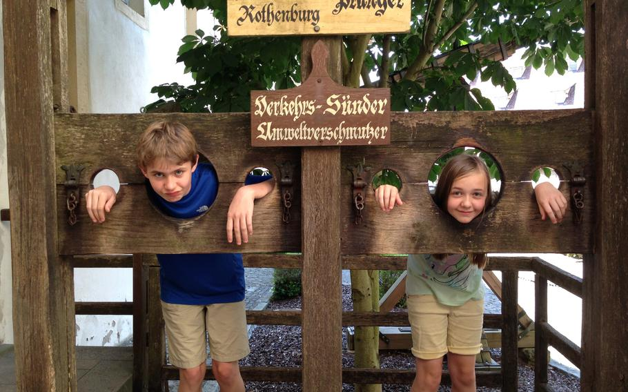My two youngest kids, Nicholas and Avery, take a few moments to experience life in a stock outside the  Criminal Museum in Rothenburg.