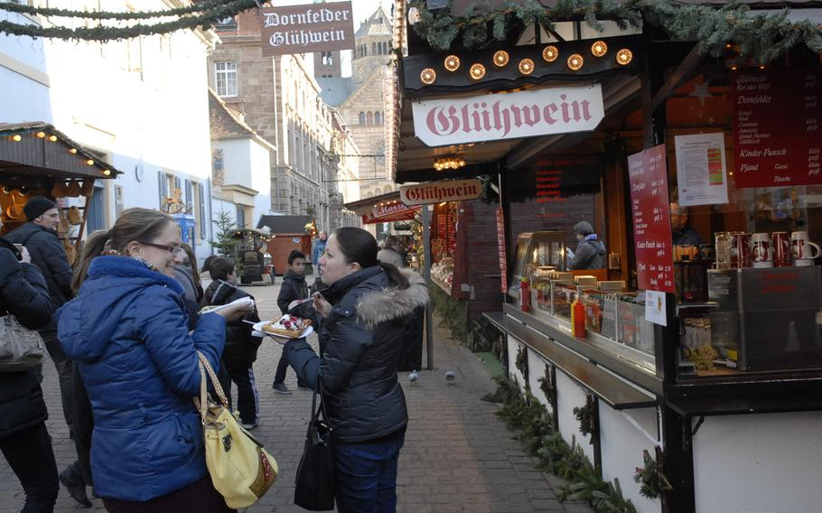 Women chat at the Speyer Christmas Market in December 2013, while one enjoys a warm waffle topped with whipped cream and fruit.