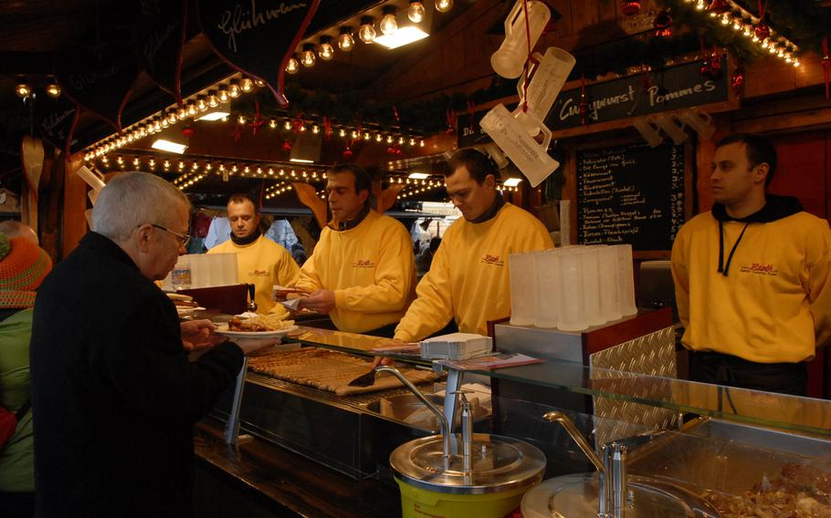 Men in yellow serve up red and white bratwurst at the Speyer Christmas Market in Speyer, Germany, in December 2013. Eating is a popular activity at the market, where vendors sell Palatinate delicacies such as potato soup and yeast dumplings.