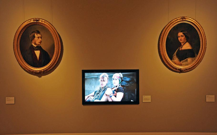 """The newest piece of art in the reopened Hesse State Museum in Darmstadt, Germany, is Martin Brand's """"Punks,"""" an HD video installation strikingly hung between 19th century portraits of Ludwig and Anna Weyland by Joseph Hartman."""