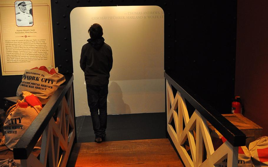 A visitor walks across a wooden bridge inside the Titanic exhibitio. The mood is somber throughout. A photograph of Titanic Captain Edward J. Smith, who went down with his ship, hangs on the wall.